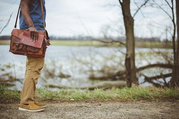 Homme debout près d'un lac tout en tenant la bible