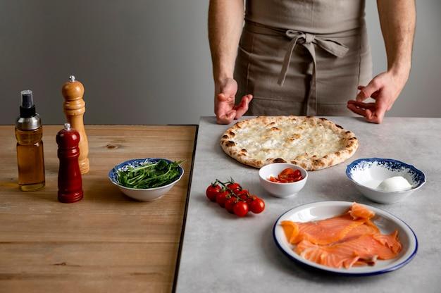 Homme debout près de la pâte à pizza cuite et des ingrédients