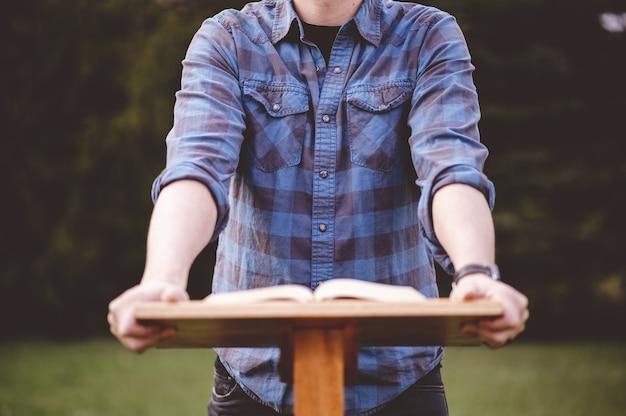 Homme debout près d'un support en bois avec un livre à ce sujet dans le parc