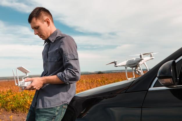 Un homme debout près de la voiture lance un drone. vol de drone dans le champ jaune