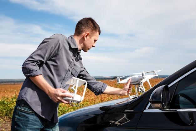 Un homme debout près de la voiture lance un drone