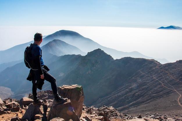 Homme debout regardant l'horizon montagnes avec brume et mer de nuages