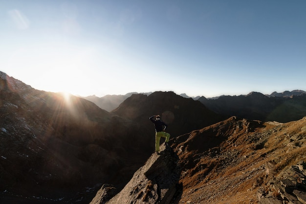 Homme debout sur un rocher au sommet d'une montagne face au soleil