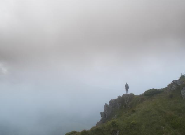 L'homme debout sur le rocher brumeux