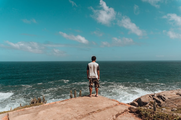 Homme debout sur les rochers entouré de verdure et de la mer sous la lumière du soleil et un ciel bleu