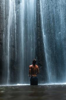 Homme debout sous une superbe cascade à bali indonésie