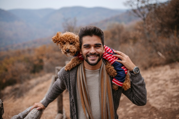 Homme debout et tenant le chien sur les épaules dans la nature.