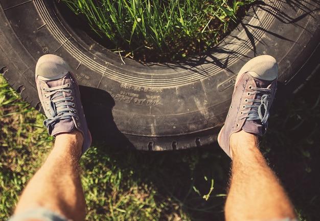 Homme debout sur un vieux pneu, photo teintée