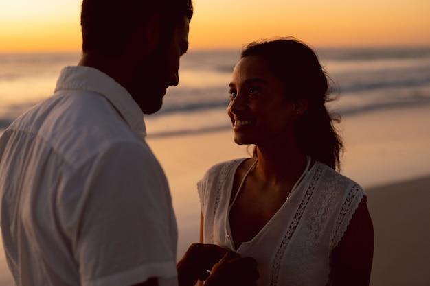 Homme déboutonnant femme haut sur la plage