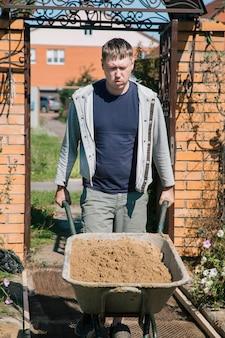 Un homme décharge du sable dans un mélange de ciment pour verser un chemin de jardin, des travaux de construction sur un terrain de jardin