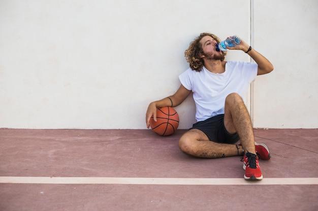 Homme décontracté avec de l'eau potable au basket