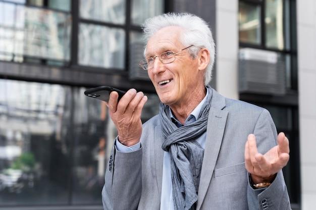 Homme décontracté plus âgé dans la ville parlant sur smartphone