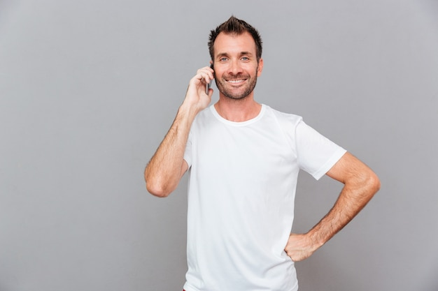 Homme décontracté souriant parlant au téléphone isolé sur fond gris