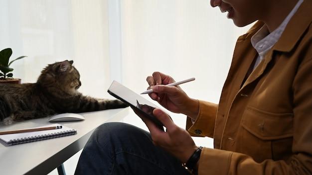 Homme décontracté tenant le câblage du stylo sur un ordinateur portable et assis avec un joli chat à la maison.