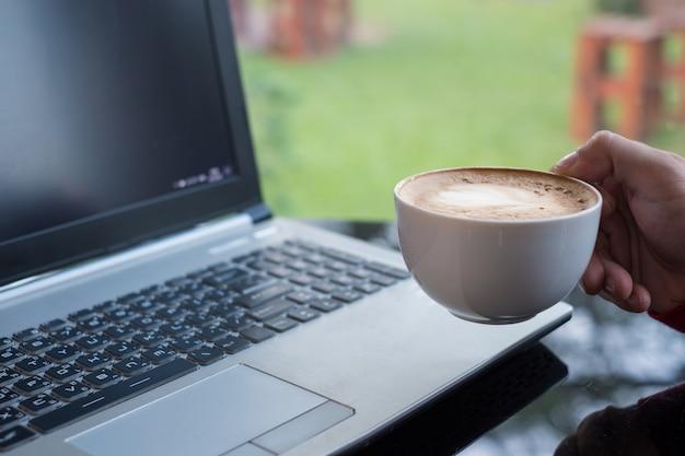 Homme décontracté tenant une tasse de café avec un ordinateur portable au bureau