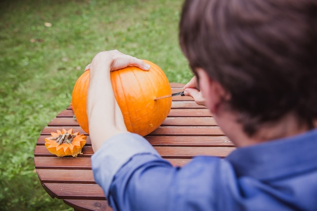 Homme découpant une grosse citrouille sur une table en bois pour halloween