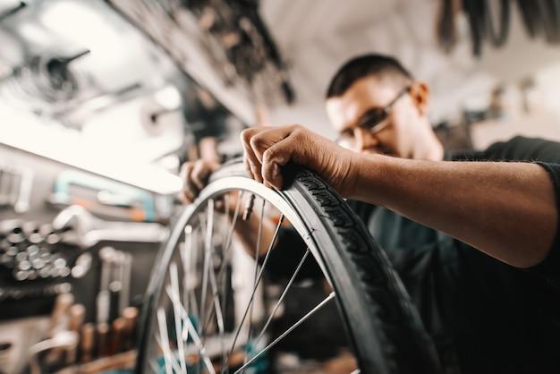 Homme dédié caucasien mettant pneu sur roue de vélo tout en se tenant dans l'atelier.