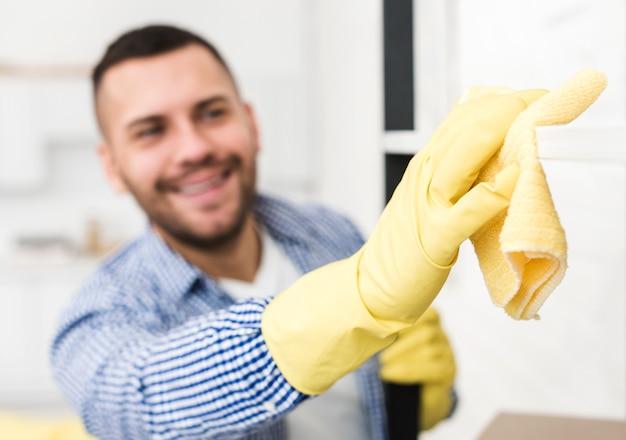 Homme défocalisé à l'aide de chiffon pour nettoyer