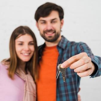 Homme défocalisé avec sa femme détenant la clé de la maison devant la caméra