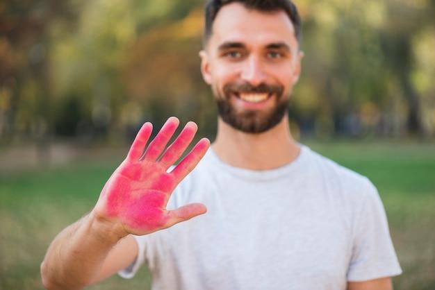 Homme défocalisé, tenant une main colorée