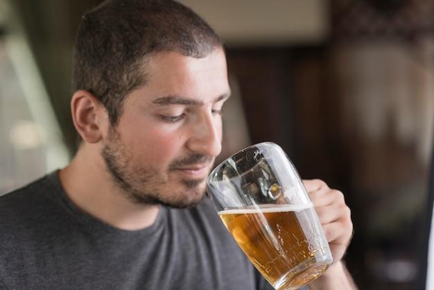 Homme dégustant une bière au bar