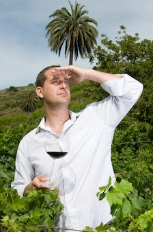 Homme dégustant du vin de ses caves dans un vignoble