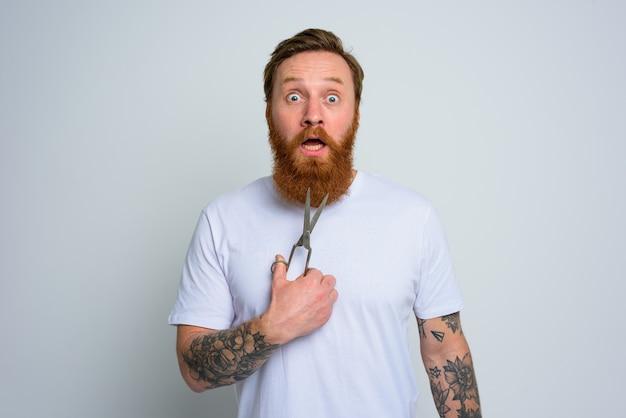 L'homme demandé avec des ciseaux est prêt à couper la barbe
