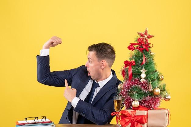 Homme demandé montrant son muscle assis à la table près de l'arbre de noël et présente sur jaune