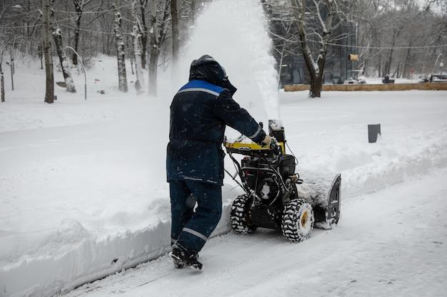L'homme de déneiger ou d'enlever la neige avec une souffleuse à neige sur une route enneigée dans le parc