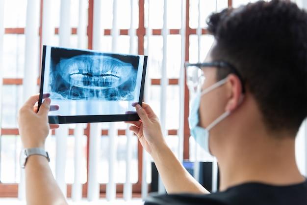 Homme dentiste analyse xray dans le bureau de la clinique de dentiste