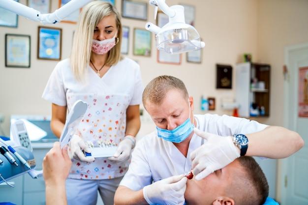Homme dentiste faisant un traitement dentaire sur un patient jeune homme. jeune assistante womam.