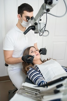 Homme dentiste avec des outils dentaires - microscope, miroir et sonde traitant les dents des patients au bureau de la clinique dentaire