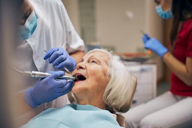 Homme dentiste avec outils dentaires et perceuse tout en prenant soin des dents du patient au bureau de la clinique dentaire