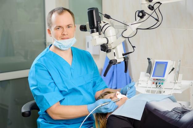 Homme dentiste travaillant au microscope à la clinique de dentiste moderne