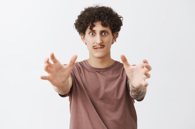 Homme avec dépendance voyant l'objet qu'il voulait si mal tirant les mains vers la lèvre mordante et regardant comme un fou sentiment de désir de le tenir dans des mains debout excité et bizarre sur un mur gris