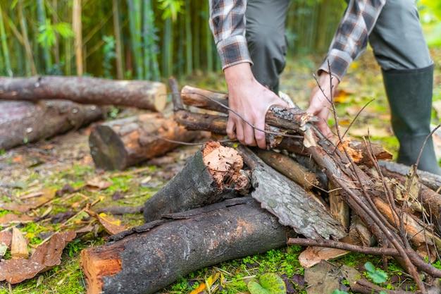 Homme déplaçant des troncs sur sa brouette jaune bûcheron bûcheron avec des bottes et une chemise carrée