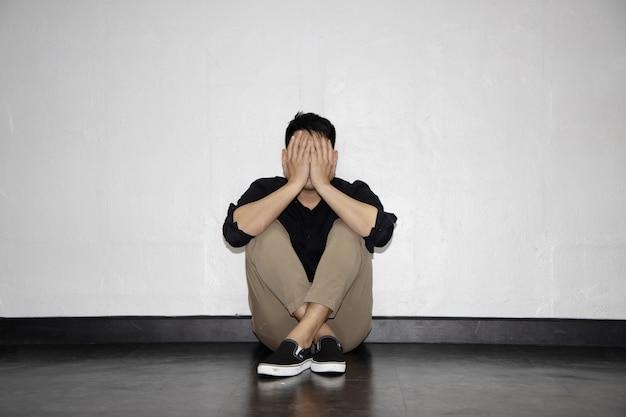 Homme de dépression assis près du mur sur le sol
