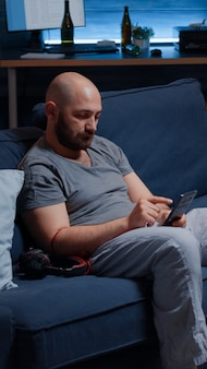 Homme déprimé écoutant de la musique à l'aide d'écouteurs assis seul