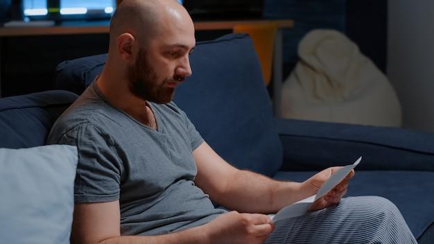 Homme déprimé stressé en colère lisant de mauvaises nouvelles dans une lettre postale