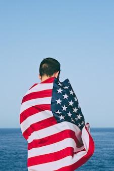 Homme de derrière enveloppé dans le drapeau américain