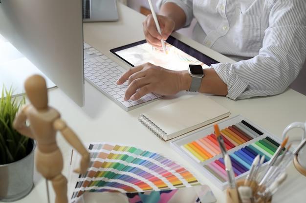 Homme designer travaillant avec une tablette dans l'espace de travail studio
