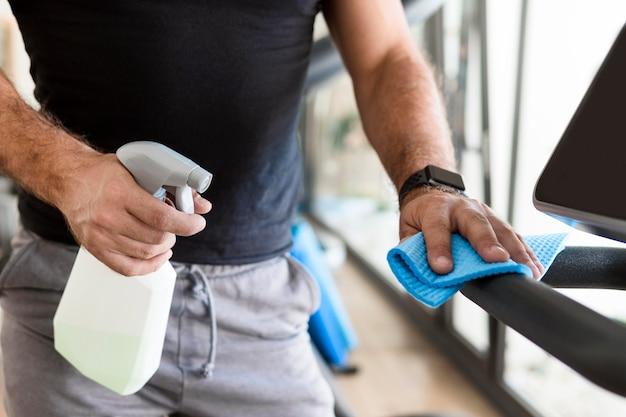 Homme désinfectant l'équipement de gym