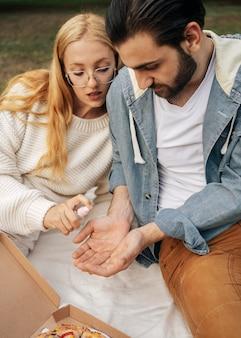 Homme désinfectant les mains de sa petite amie avant de pique-niquer