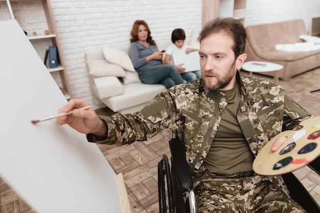 Homme en dessin en fauteuil roulant. il a de la peinture et un pinceau dans les mains.
