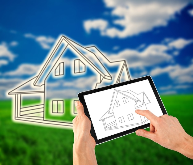 Homme dessinant un plan de sa maison sur la tablette comme ipad
