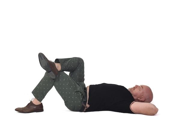 Homme détendu allongé sur un sol sur fond blanc