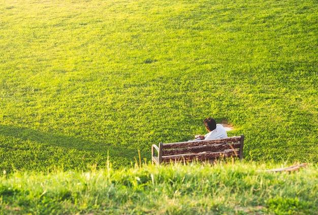 Homme de détente assis sur un banc de parc avec de l'herbe très verte sur une journée ensoleillée.