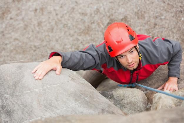 Homme déterminé escaladant une paroi rocheuse