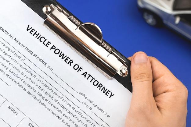 L'homme détient le formulaire de demande de procuration de vechile. bureau et presse-papiers avec accord. photo vue de dessus