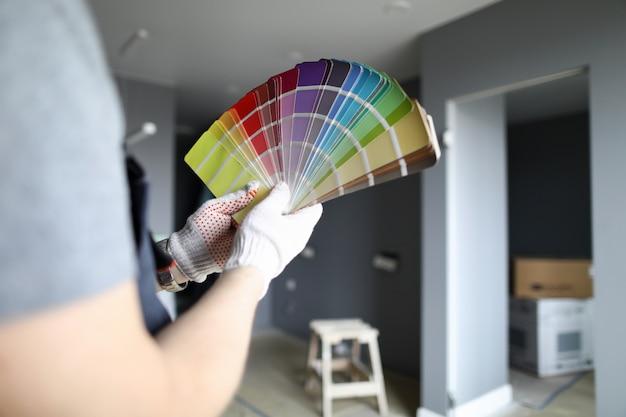 L'homme détient la palette dans le choix de la couleur pour la réparation